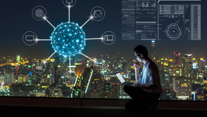 Asian businessman sitting and using the laptop for online shopping with omni channel over the cityscape background at night time, Business success and technology concept